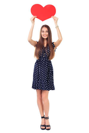 Full length portrait of beautiful smiling young woman in polka dot dress holding red heart over her head isolated on white background. Valentines day. photo