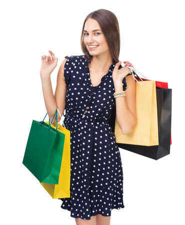 Portrait of young beautiful smiling woman holding many colorful shopping bags, showing hello sign, isolated on white background photo
