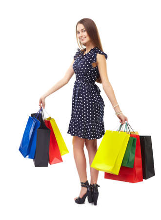 Full length portrait of young beautiful smiling happy woman holding many colorful shopping bags,turning around, isolated on white background photo