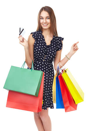 Portrait of young beautiful smiling happy woman with two credit cards and many colorful shopping bags pointing finger isolated on white background photo