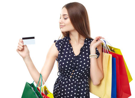 Portrait of young beautiful smiling woman with credit card and many colorful shopping bags isolated on white background photo