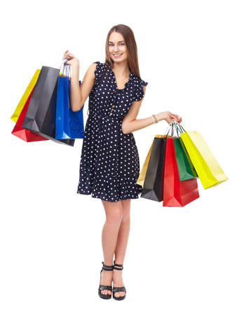 Full length portrait of young beautiful smiling happy woman holding many colorful shopping bags isolated on white background photo
