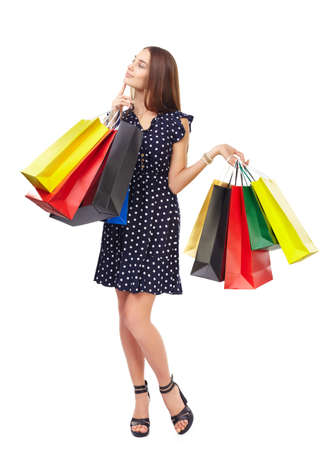 Full length portrait of young beautiful smiling woman holding many colorful shopping bags thinking with finger on chin isolated on white background photo