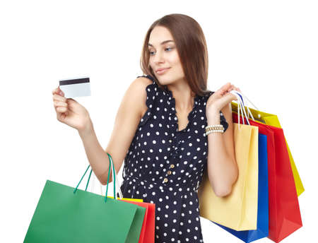 spender: Portrait of young beautiful smiling woman with credit card and many colorful shopping bags isolated on white background