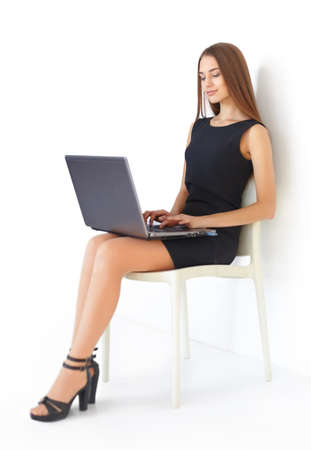 Beautiful young business woman sitting on chair working with laptop on white background photo