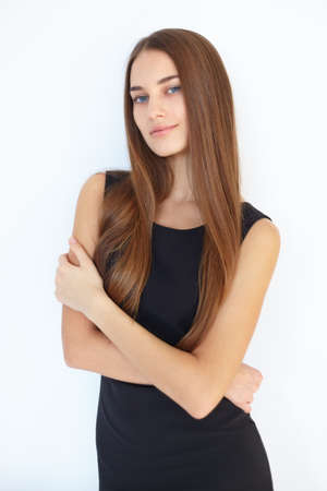 elegance fashion girls look sensuality young: Portrait of beautiful young smiling woman with long straight hair in black dress isolated on white background