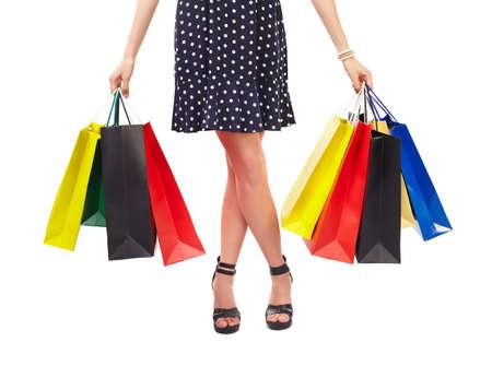 comprando zapatos: Vista de la cintura hacia abajo de mujer con bolsas de colores aislados sobre fondo blanco