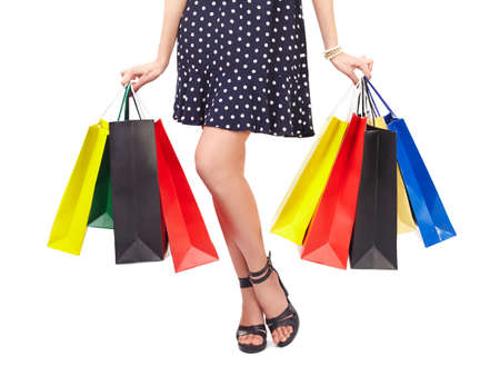 Waist-down view of woman holding colorful shopping bags isolated on white background photo