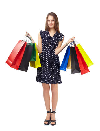 Full length portrait of young beautiful woman with dissatisfied expression holding many colorful shopping bags isolated on white background