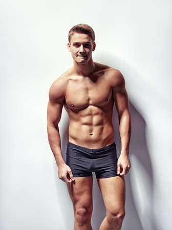 Portrait of a young sexy muscular man in underwear against white wall photo