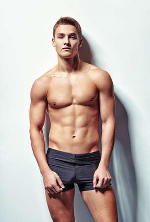 Chân dung của một người đàn ông cơ bắp sexy trẻ trong quần lót chống lại bức tường trắng