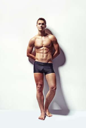 full: Retrato de cuerpo entero de un hombre musculoso sexy en ropa interior contra la pared blanca