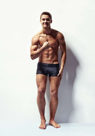 full length: Volledige lengte portret van een jonge sexy gespierde man in ondergoed toont zijn spieren tegen witte muur