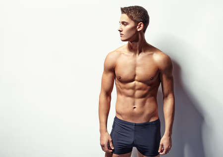 Portrait of a young sexy muscular man in underwear looking away against white wall with copy space Stock Photo
