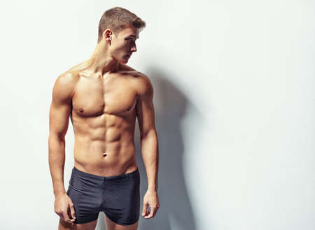 Portrait of a young sexy muscular man in underwear looking away against white wall with copy space photo