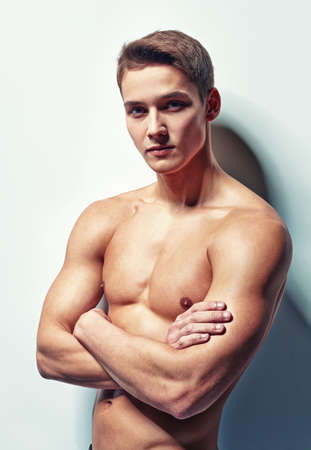 Portrait of young muscular man with naked torso standing with hands folded against white wall photo