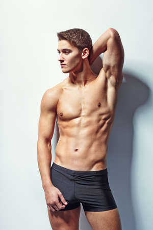 Portrait of a young sexy muscular male model in underwear against white wall in sensual pose his hand behind his head Stock Photo