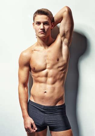 Ritratto di un giovane sexy modello maschile muscolare in biancheria intima contro il muro bianco in posa sensuale una mano dietro la testa