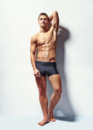 modelo desnuda: Retrato de cuerpo entero de un modelo sexy muscular varón joven en ropa interior contra la pared blanca en sensual pose su mano detrás de su cabeza
