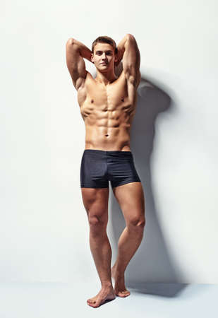 Full length portrait of a young sexy muscular male model in underwear against white wall in sensual pose his hands behind his head