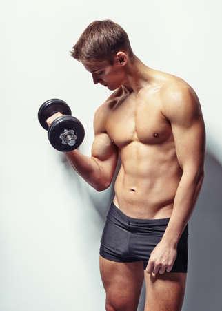 Chân dung của người đàn ông thể hình trẻ tập thể dục với tạ cho đào tạo bắp tay của mình chống lại bức tường trắng
