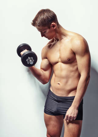 Portrait of young bodybuilder man exercising with dumbbell for training his biceps against white wall