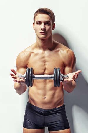 Portrait of young bodybuilder man offering dumbbell for training against white wall photo