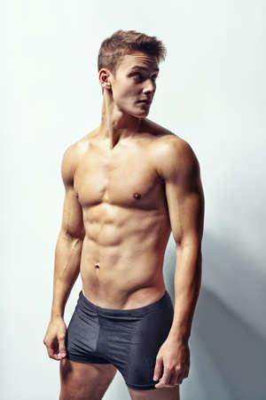 Chân dung của một thanh niên cơ bắp trong đồ lót nhìn đi chống lại bức tường trắng