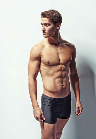Portrait of a young muscular man in underwear looking away against white wall Stock Photo