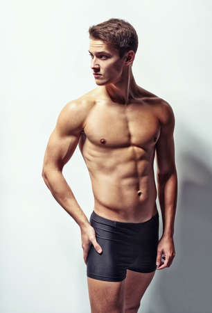 Portrait of a young sexy muscular man in underwear hand touch hips looking away against white wall Stock Photo