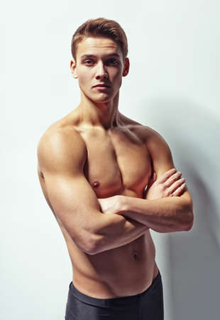 Portrait of a young muscular man with naked torso standing with arms crossed against white wall Stock Photo