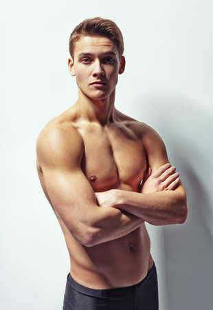 hombre desnudo: Retrato de un hombre musculoso joven con el torso desnudo de pie con los brazos cruzados contra la pared blanca