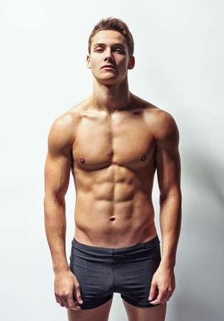 Chân dung của một người đàn ông trẻ tuổi cơ bắp trong quần lót chống lại bức tường trắng