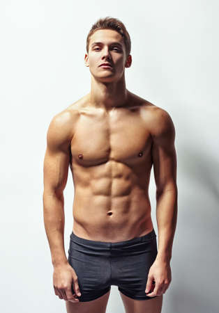 Portrait of a young muscular man in underwear against white wall