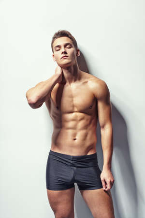 Portrait of a young muscular man in underwear with neck pain and eyes closed against white wall photo