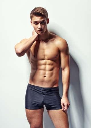 Chân dung của một thanh niên cơ bắp trong đồ lót với đau cổ chống lại bức tường trắng