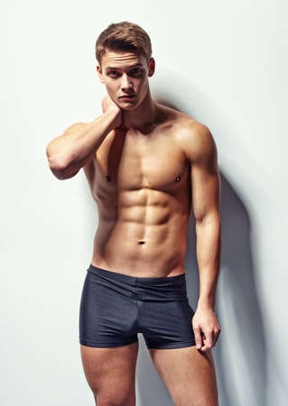 Portrait of a young muscular man in underwear with neck pain against white wall