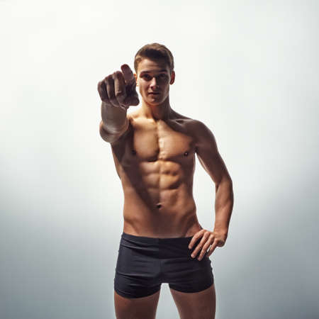 Bottom view of  young sexy muscular man in underwear pointing forward on white background photo