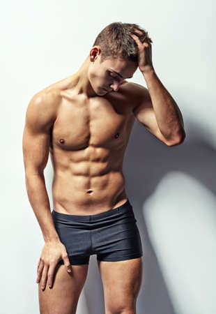 man underwear: Portrait of depressive young muscular man in underwear with headache against white wall Stock Photo