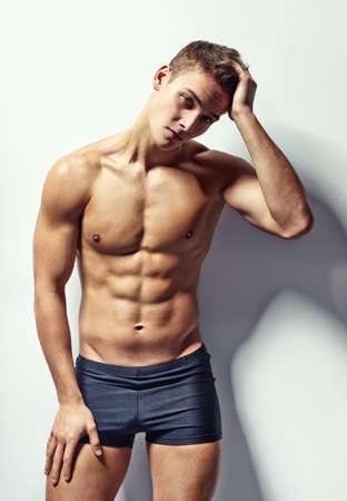 Retrato de homem musculoso jovem depressivo na cueca com dor de cabe