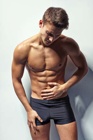 abdominal wall: Portrait of young muscular man in underwear whis abdominal pain against white wall Stock Photo