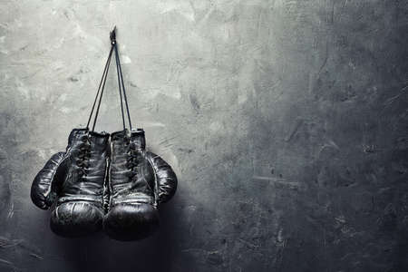 boxing sport: old boxing gloves hang on nail on texture wall with copy space for text  Retirement concept