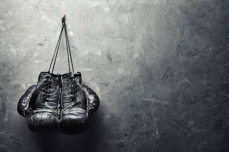 fitness training: oude bokshandschoenen hangen spijker op textuur muur met kopie ruimte voor tekst Pensioen-concept Stockfoto