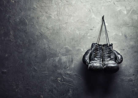 古いボクシング グローブ コピーのテキストの概念は退職のための領域を持つテクスチャ壁上の爪にハングアップします。