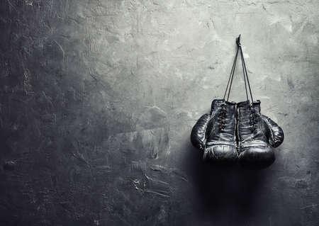 boxeadora: viejos guantes de boxeo se cuelguen de las u�as en la pared de la textura con copia espacio para el concepto de retiro de texto