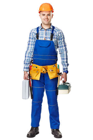 Full length portrait of young male construction worker with toolboxes wearing protective clothes, helmet and tool belt isolated on white background photo