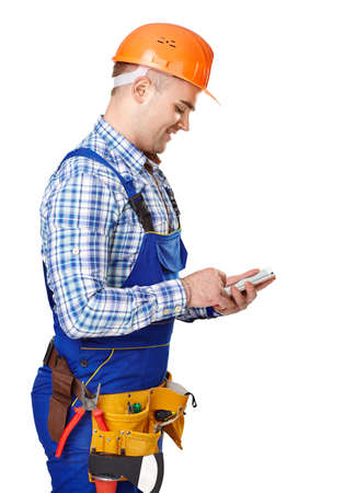 Side view portrait of young male construction worker with smartphone wearing protective clothes, helmet and tool belt isolated on white background photo