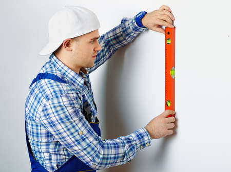 Young construction worker using spirit level on white wall photo