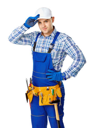 Portrait of young male construction worker with tool belt touching his white cap isolated on white background