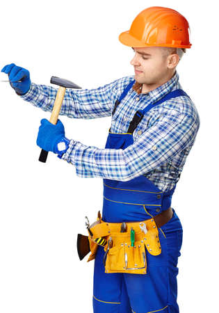 Young working man wearing protective clothes,gloves and helmet with hammer driving a nail in wall isolated on white background photo